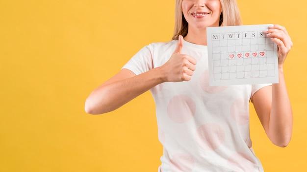 Plano médio de mulher mostrando seu calendário menstrual e bate