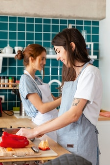 Plano médio de mulheres felizes cozinhando juntas