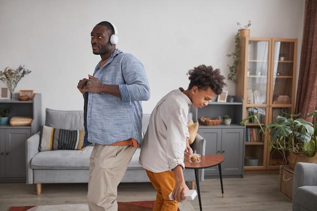 Plano médio de um homem afro-americano e um adolescente se divertindo dançando na sala de estar de casa