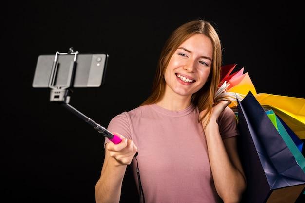 Plano médio de uma mulher tirando uma selfie com suas sacolas de compras