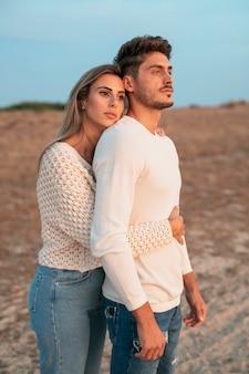 Plano médio do casal olhando para longe