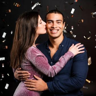 Plano médio do casal se beijando na festa de ano novo