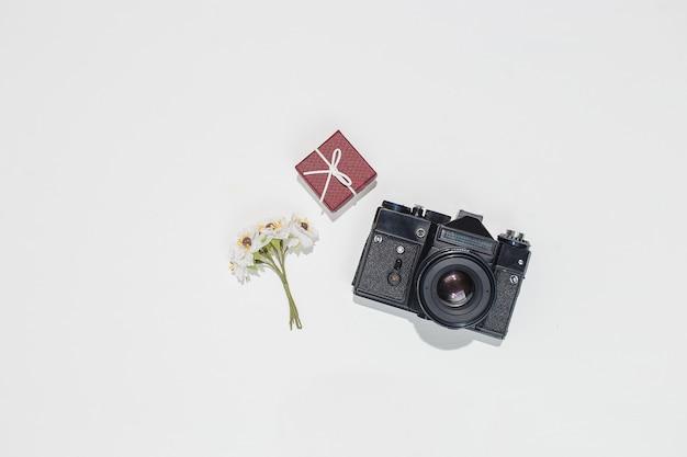 Plano minimalista colocar composição com câmera retro, caixa de presente vínica e flor de campo de primavera em fundo branco.