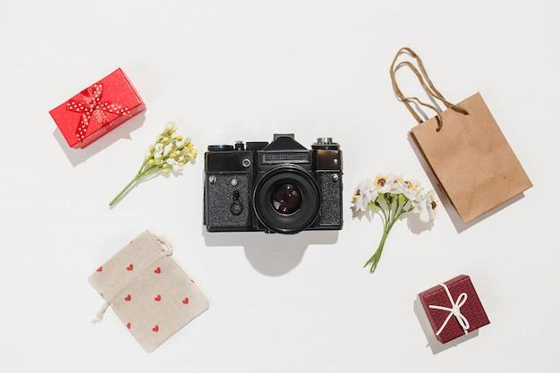 Plano minimalista leiga composição com câmera retro, caixas de presente vermelhas, saco de artesanato, saco de lona com formas de coração vermelho e primavera campo de flores sobre fundo branco.