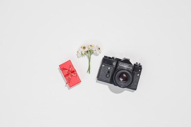 Plano minimalista leigos composição com câmera retro, caixa de presente vermelha e primavera campo de flores sobre fundo branco.