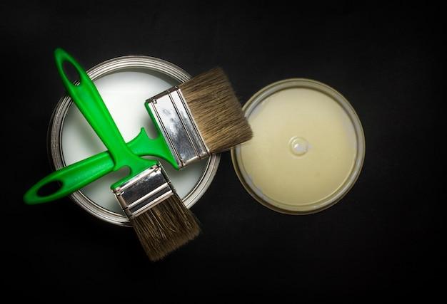 Plano plano, em um fundo preto texturizado, dois pincéis verdes colocados um em cima do outro em uma lata de tinta de ferro.