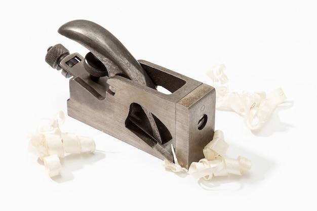 Plano velho do ferro e aparas de madeira isolados no branco. ferramenta de carpinteiro vintage