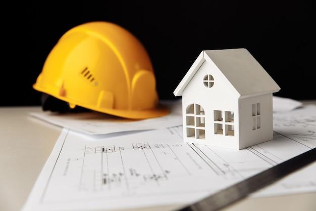 Planos de construção com capacete de proteção e casa branca em uma mesa