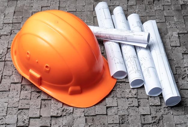 Planos de papel de arquitetura com capacete