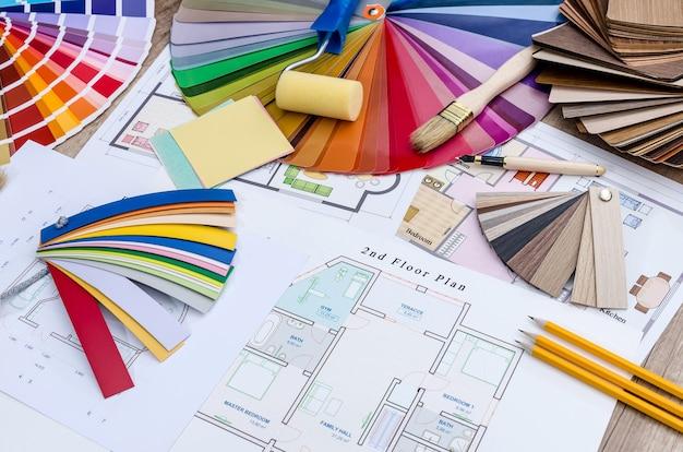 Planta da casa, desenhos coloridos e de madeira e amostras com ferramentas de trabalho