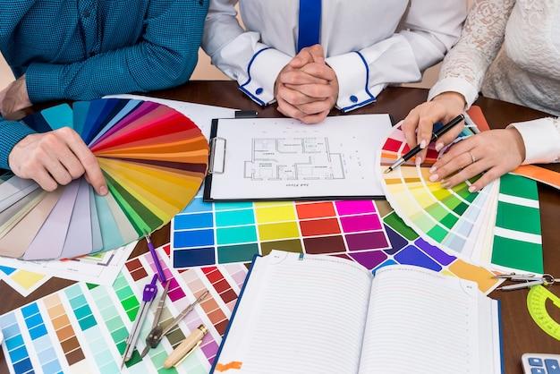 Planta da casa, equipe de designers, local de trabalho e amostradores de cores