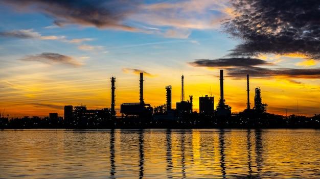 Planta da indústria de refinaria de petróleo e gás com iluminação de brilho e nascer do sol pela manhã