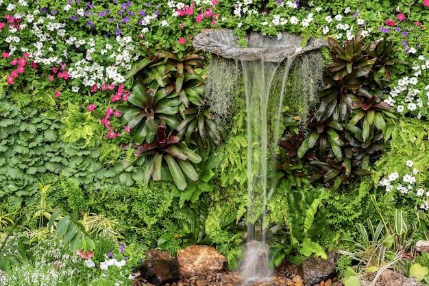 Planta de folhas verdes exuberantes verticais e parede decorativa de jardim de flores com cachoeira
