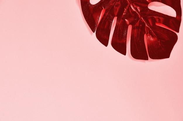 Planta de monstera brilhante metal vermelho sobre rosa pastel. colorfull cenário em cores da moda.