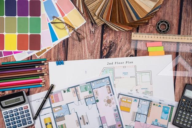Planta de papel do chão da casa e amostrador de madeira, pedágios de trabalho, calculadora na mesa de madeira.