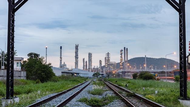 Planta de produção industrial de petróleo e gás com a ferrovia em primeiro plano à noite