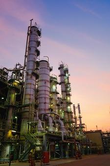 Planta de refinaria de petróleo e gás ou indústria petroquímica no pôr do sol no céu, fábrica à noite, fabricação de instalações industriais de petróleo