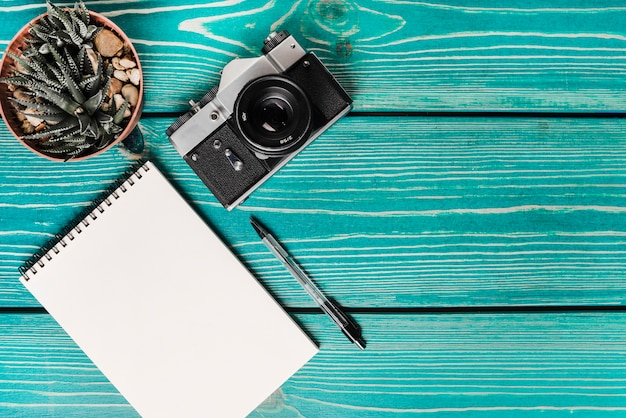 Planta de vaso de cacto; câmera; almofada de nota em espiral e caneta na prancha de madeira turquesa