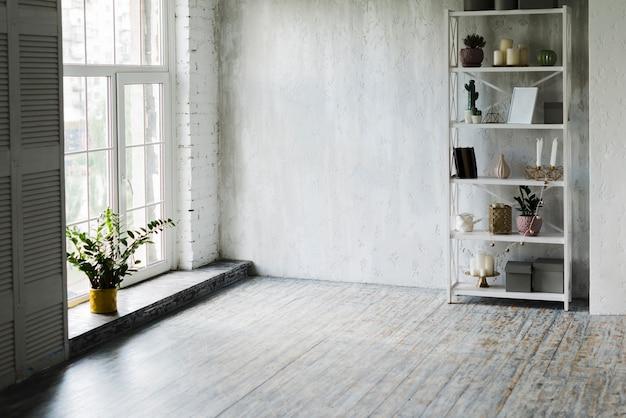 Planta em vaso perto da janela e prateleira na sala