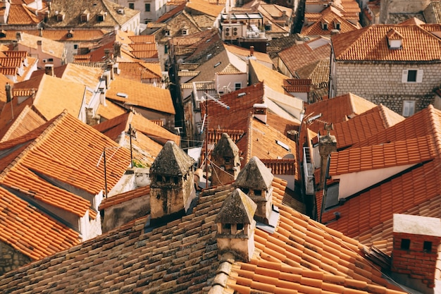 Planta geral de velhos telhados laranja de casas com chaminés e antenas surradas