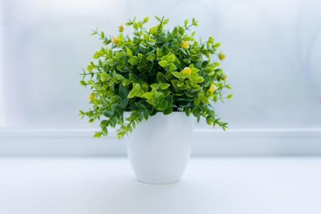 Planta interior artificial verde em vaso branco