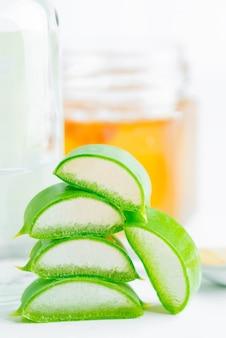 Planta orgânica natural de vera do aloés do close-up cortada para o líquido cosmético caseiro contra o branco.