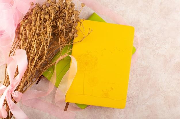 Planta peganum harmala seca e com laço rosa e caderno na mesa rosa foto colorida