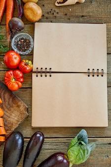 Planta plana do ingrediente para cozinhar, vegetais ao redor do livro de receitas
