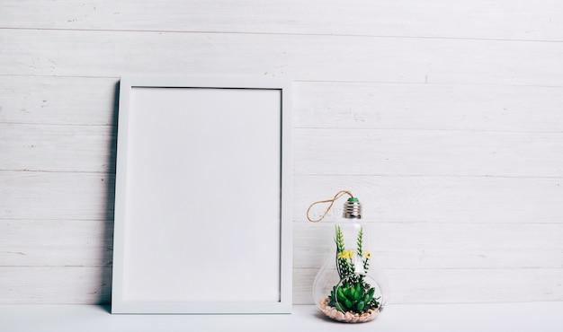 Planta suculenta em miniatura dentro da lâmpada de pendurar vidro perto da moldura branca contra a parede de madeira
