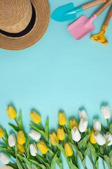 Plantando flores da primavera ferramentas de jardinagem tulipas amarelas brancas cópia espaço vista superior colher fundo azul conceito de verão