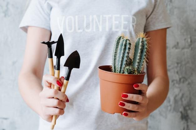 Plantando voluntário. cuidado e proteção da natureza. mulher com planta de casa e ferramentas de jardim.