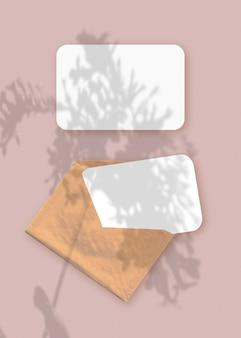 Plantar sombras no envelope com duas folhas de papel branco texturizado em um fundo de mesa rosa
