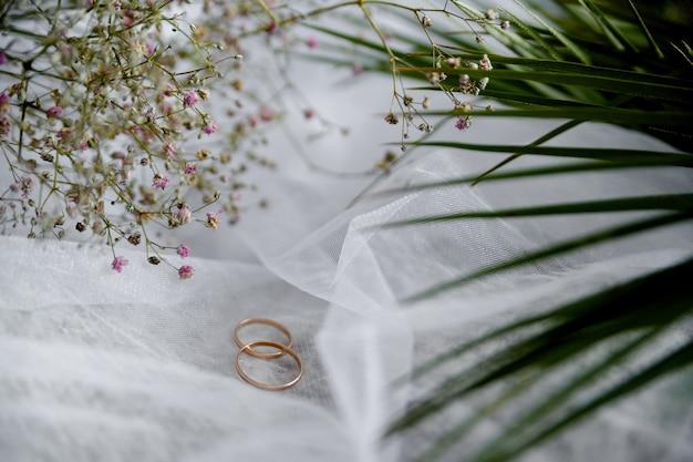 Plantas de véu de duas alianças de casamento na natureza morta
