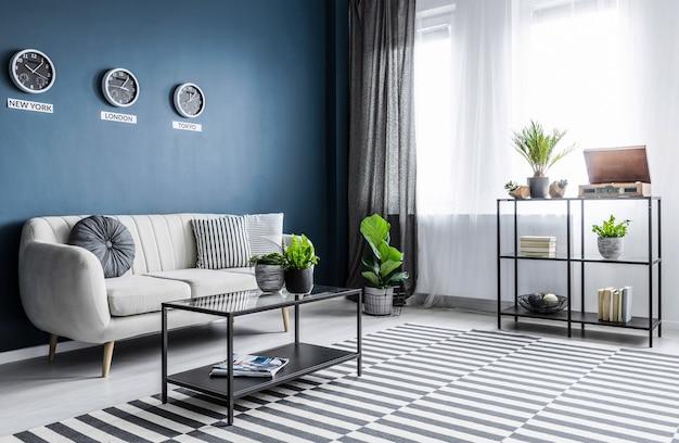 Plantas e carpete estampado no interior da sala de estar azul brilhante com relógios acima do sofá bege