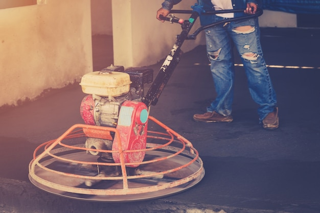 Plasterer trabalhando usando máquina de depuração para chão de cimento com tonificado vintage