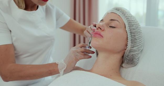 Plasticidade do contorno dos lábios, aumento dos lábios, introdução de enchimento de ácido hialurônico na mulher no centro de spa.