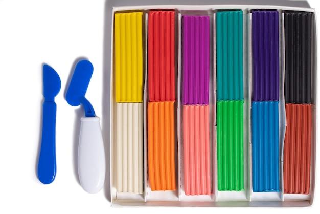 Plasticina multicolorida em uma caixa de 12 cores em um fundo branco