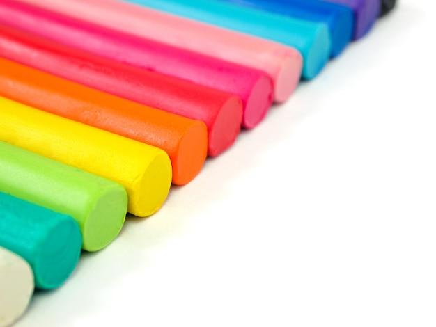 Plasticine do miúdo colorido no fundo branco, massa de modelar colorida da massa