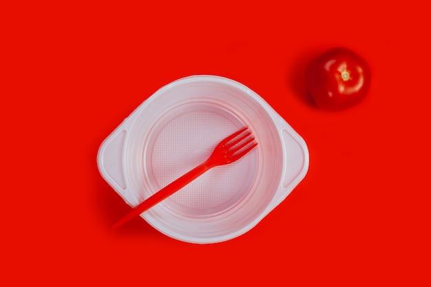 Plástico branco isolado prato vazio garfo tomate