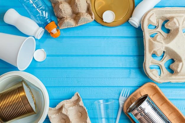 Plástico colorido, latas de metal, papel, resíduos de papelão sobre fundo azul. conceito ecológico com espaço de cópia