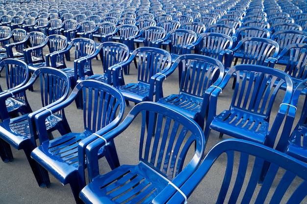 Plástico contratar cadeiras em uma linha de cor azul
