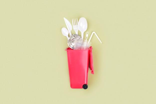 Plástico de uso único branco no recipiente de lixo sobre fundo verde. conceito de reciclagem de plástico.