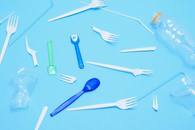 Plástico descartável branco na lata de lixo em fundo azul