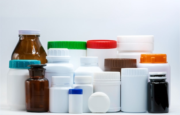 Plástico médico e frasco ambarino no fundo branco com etiqueta em branco. indústria de embalagens farmacêuticas. recipiente para garrafas de vitaminas e suplementos. frasco de comprimidos com tampa laranja, verde, azul e vermelha.