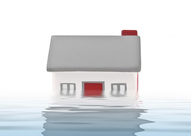 Plástico modelo da casa submergido sob a água
