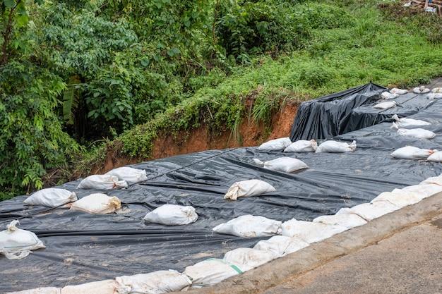 Plástico preto com saco de areia coberto na estrada em colapso