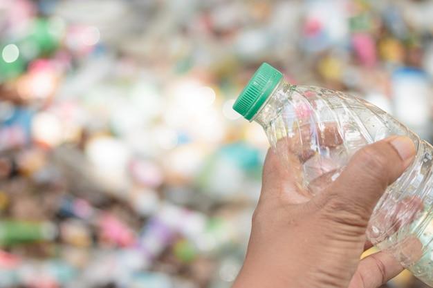 Plástico reciclável da mostra da posse da mão para reciclar a reutilização do conceito.