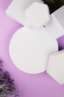 Plataforma branca com formas geométricas e flores e monstera em um fundo roxo