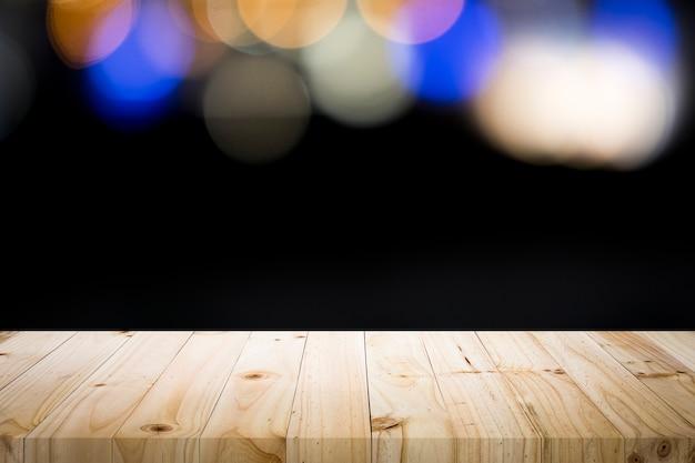Plataforma de mesa de madeira vazia no bokeh perto.