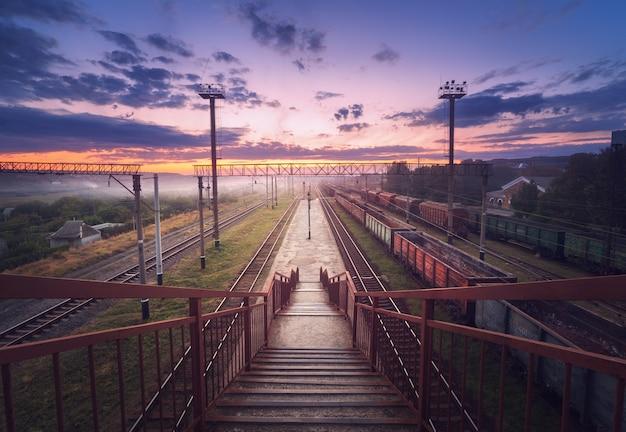 Plataforma de trem de carga ao pôr do sol. ferrovia na ucrânia. estação ferroviária